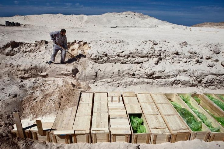 A rebel gravedigger buries a row of more than 300 Qadafi government troops killed in combat in the city of Misrata, Libya in 2011.
