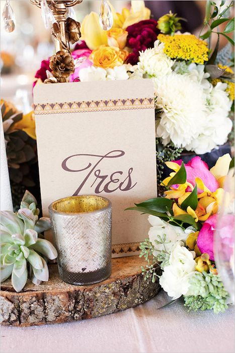 A centerpiece overflowing with flowers has a Latin touch with the addition of Spanish table numbers. Source: Luna Photo #centerpieces #Latintheme #tablenumbers