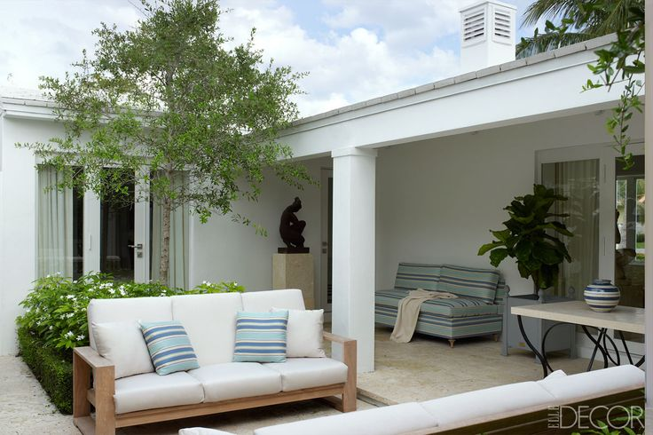 """The living room has doors on either side that open onto the lush tropical property (two palm trees wave on the front lawn). The house occupies just 2,000 square feet, but the grounds are spacious; in the backyard—his """"inner sanctum,"""" as he describes it—Aparicio has installed a pool, a pergola with seating, and a terrace. """"The house is basically a large pleasure pavilion in a garden, which is just how I had envisioned it,"""" he says. The terrace sofas are custom made, the striped fabric is by…"""