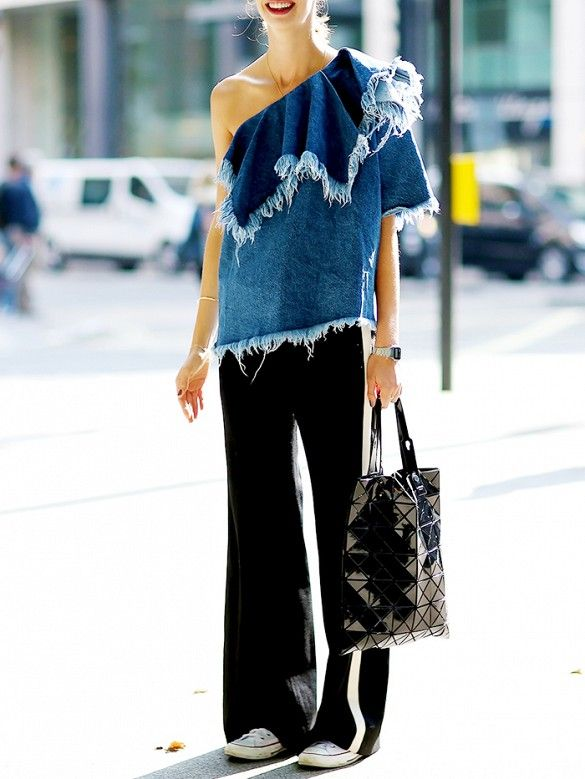 A frayed denim one-shoulder blouse is worn with wide-leg pants, Converse sneakers, and a paneled tote bag