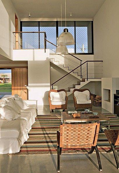 Com pé-direito duplo de 5,20 m, o espaço tem lareira de alvenaria e janelas altas que proporcionam a ventilação cruzada. A escada de concreto possui guarda-corpo de alumínio. Projeto do escritório Seferin