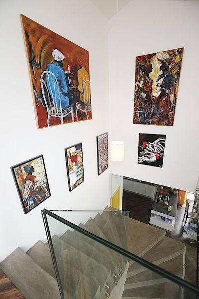 Schodiště z obývacího pokoje do patra lemují pestré obrazy afrických umělců, které spoluvytvářejí exotickou atmosféru. Z přízemí jsou viditelné díky prosklenému zábradlí.