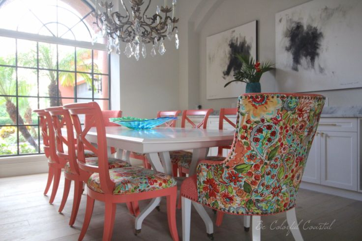Colorful coastal dining room. Coral upholstered chairs with a light gray dining table.