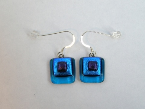 Paula Woodward - These earrings are made from three layers of fused glass. A transparent turquoise base with layers of aquamarine and blue dichroic glass on top.   They are lightweight to wear, are finished with sterling silver earwires, and match the Turquoise Layered Pendant. £16