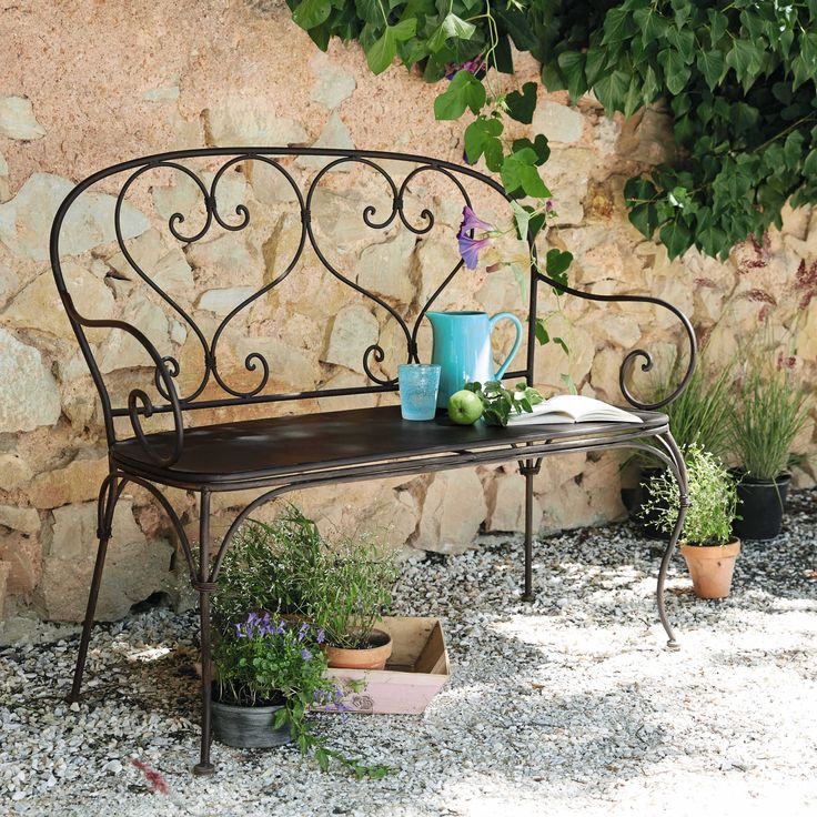 Wrought iron chairs with upholstered cushions at an outdoor seating area. I love the curly back!