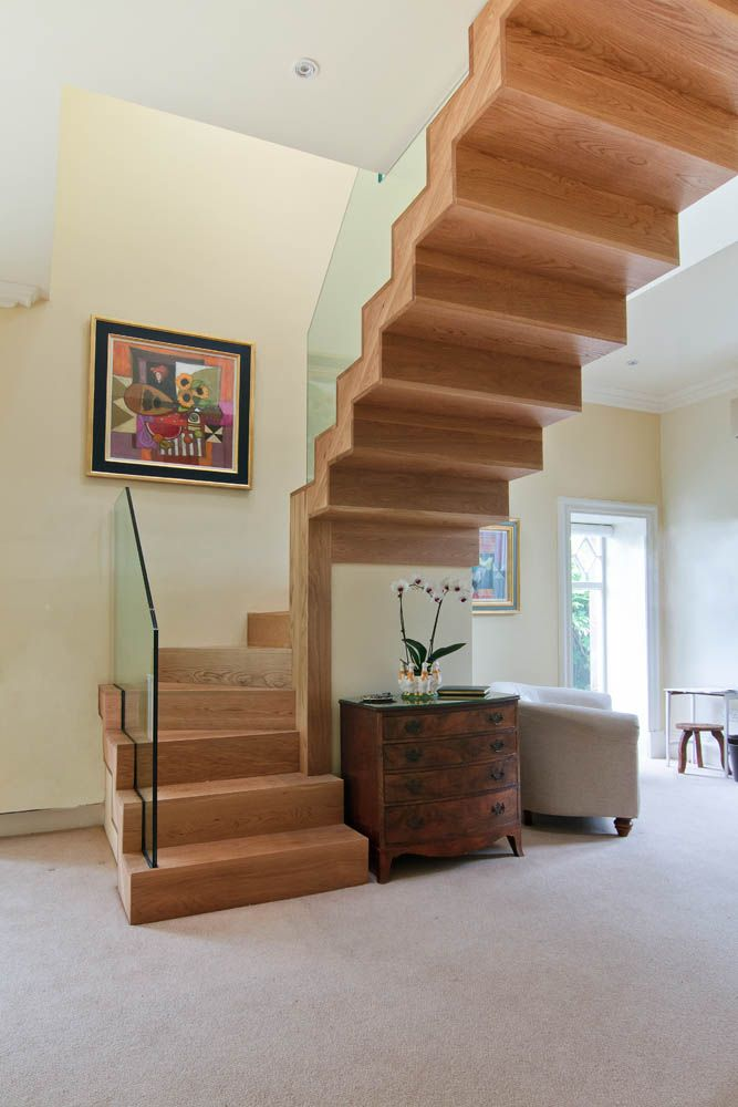 Solid American white oak timber sawtooth winder stair with inserted glass balustrading. - stockwell-ltd -uk