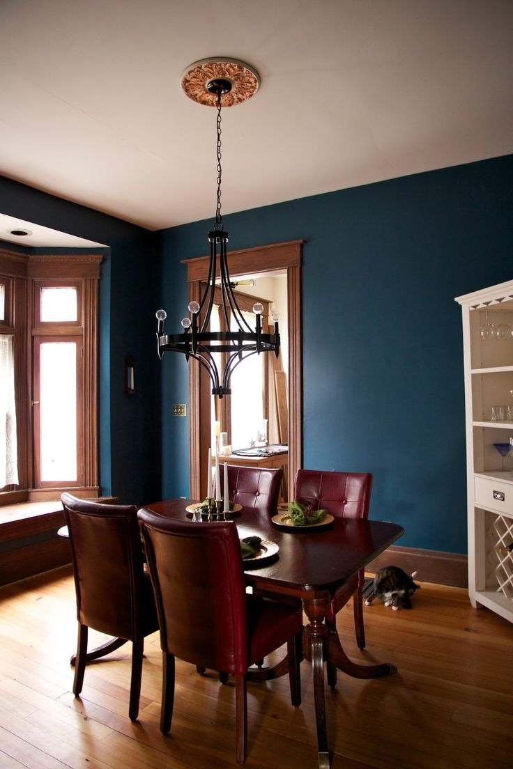Dark teal wall paint and unpainted wooden trim for the dining room.