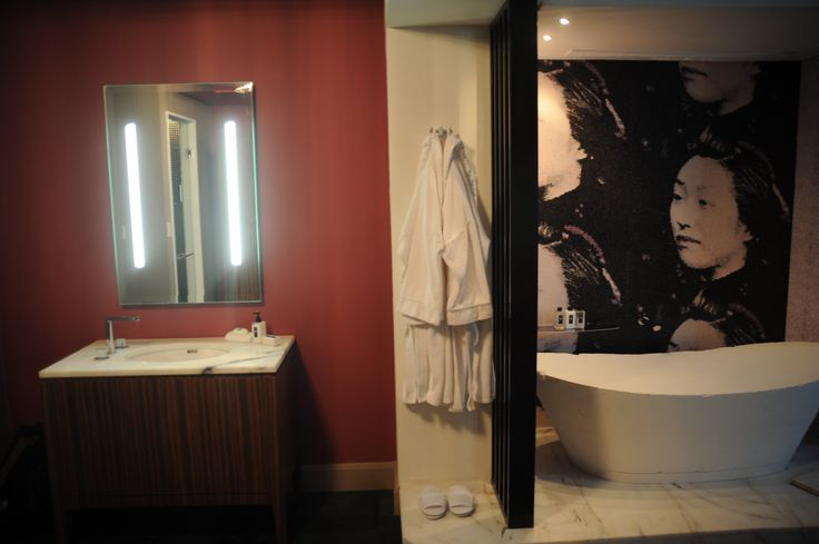 The dark Chinese wallpaper compliments the stone bath tub perfectly and evokes a luxurious feel to the bathroom.