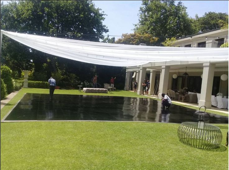 A black vinyl floor installed beneath a marquee directly on top of the lawn. Certainly does add some chic elegance to the look. #connectafloorcape #eventflooringcapetown