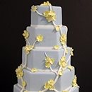 This light pink fondant cake is trimmed with silver ribbon and swathed in  handcrafted sugar hydrangeas, roses and Calla lilies in shades of pink and  cream.