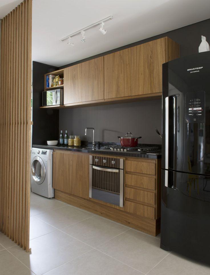 Embutir os eletrodomésticos em armários planejados amplia a cozinha, que se integra de maneira homogênia à área de serviço, criando uma identidade visual única para os espaços integrados.