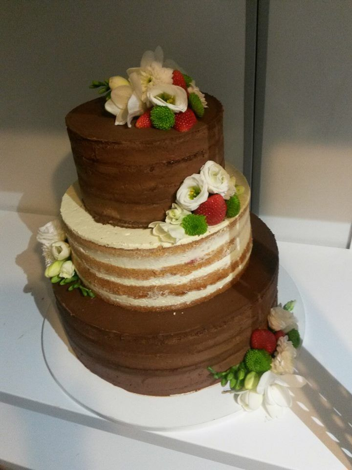 Dvoubarevný naked cake ozdobený květinami a jahodami.