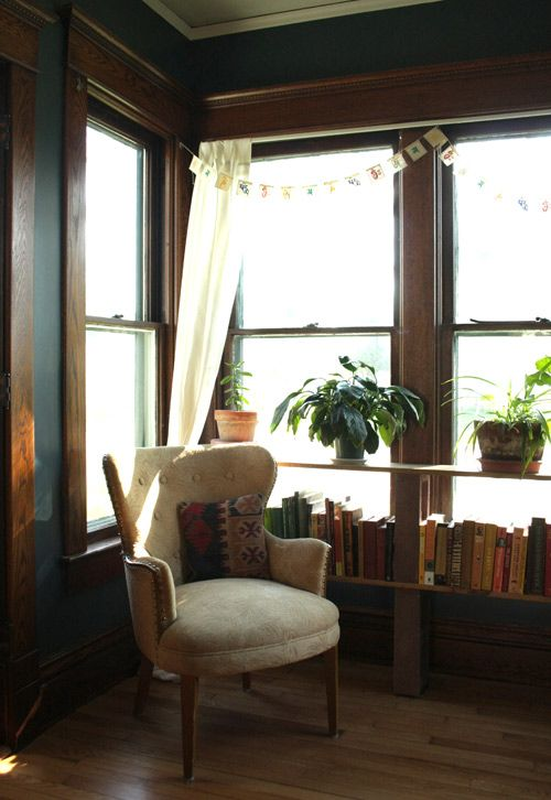 love the row of house plants and books. much less imposing than a floor-to-ceiling bookshelf would be