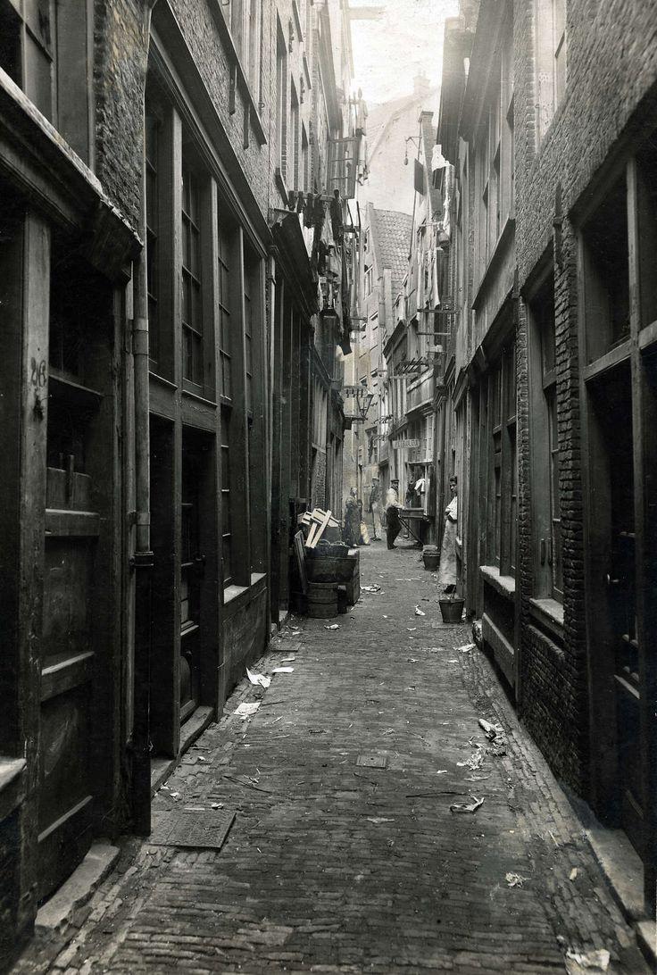 Steden: Klein Hemelrijk ( bij het Kattegat/Singel). Armoedige steeg in hartje Amsterdam, met enkele bewoners in de deuropening. Amsterdam, N...