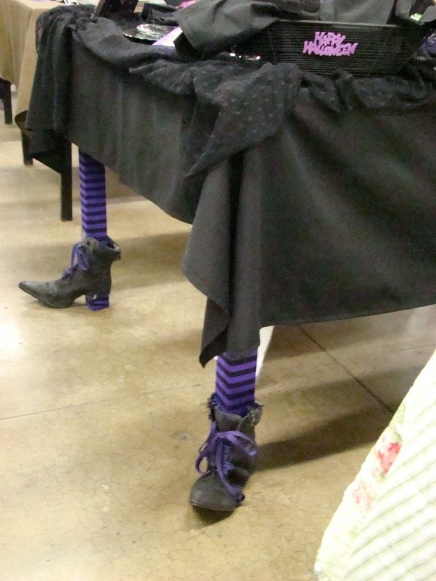 Put socks and witch shoes on the legs of a table. | 24 Surprisingly Easy Halloween Party DIYs