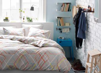 Небольшая спальня с двуспальной кроватью, вешалкой для одежды, полками, крючками, зеркалом, светильниками и лестницей-табуретом