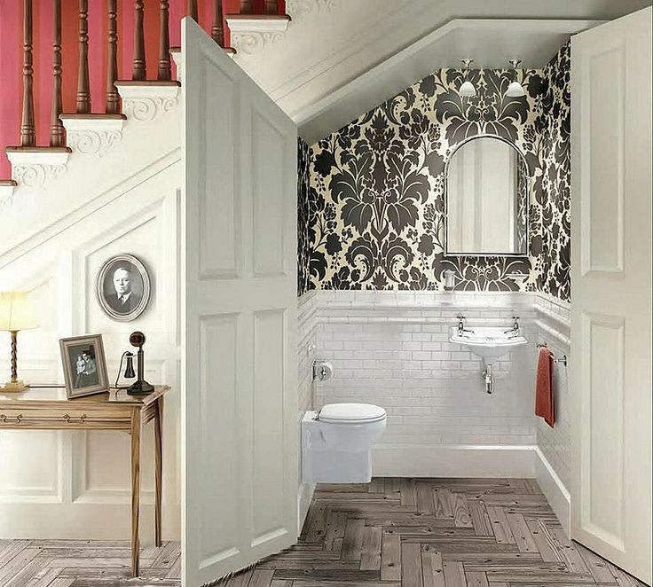 B & W powder room with Wall-mounted fixture, white subway tile, tiny sink. All under stairwell space