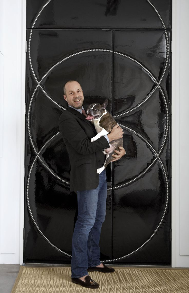 Heissmann with his dog Samson in front of the entrance doors, covered in a patent leather by Dualoy and trimmed with nailheads to distract the eye from the doors' asymmetry. Read more about Heissman's inspiration for this space here. This story originally appeared in the November 2015 issue of House Beautiful. For more details, see Resources.   - HouseBeautiful.com