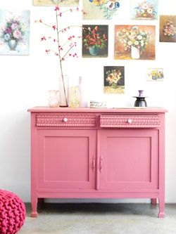A pink cabinet with flower paintings above it