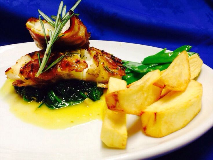 Merluzzo Raffinato - Oven backed cod chunks wrapped in pancetta. Served with a white wine sauce, on sautéed baby spinach with long roast potato chips