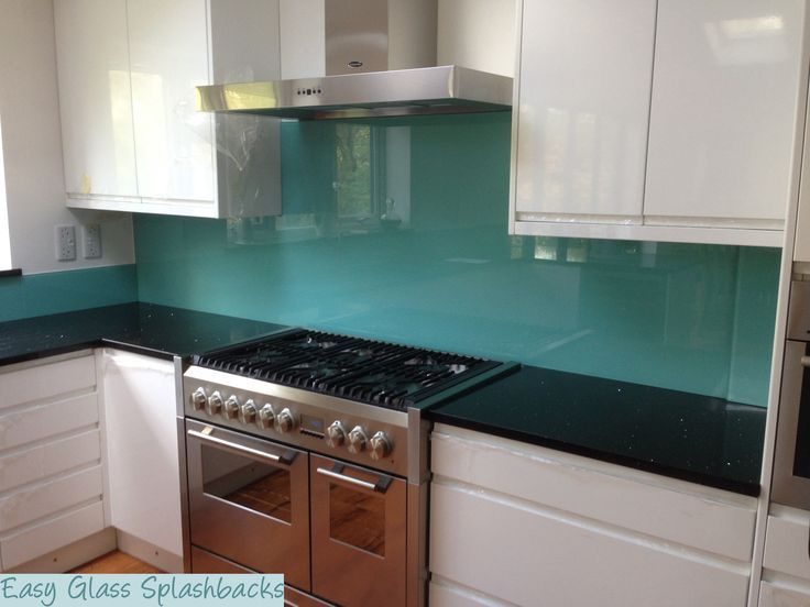 Turquoise coloured glass splashback in a White Kitchen with dark Worktop. Visit easyglasssplashbacks.co.uk to discover more.