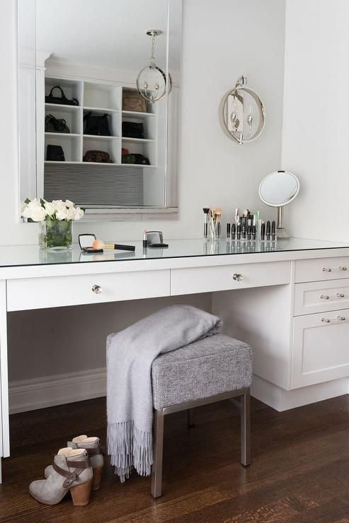 Chic dressing room features a built-in make up vanity topped with a mirror paired with a gray modern stool placed under a beveled mirror.
