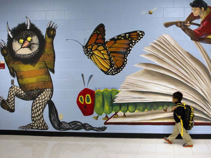 Caleb Fernandez walks past a mural on the first day of school at Thurgood Marshall Elementary on Aug. 26 in Houston.