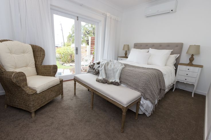Master bedroom with a comfy wicker occasional chair, upholstered bed end and…