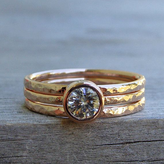 A sparkly 5mm Forever Brilliant moissanite sits in a low, straight-sided bezel on a 1.5mm round hammered/polished 14k rose gold band. Two