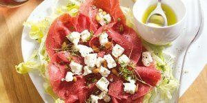 Rundercarpaccio gevuld met salade naar keuze en dichtgeknoopt met geblancheerde stengels van bieslook.