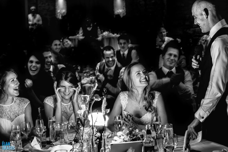 Guests laughing at wedding Speeches  at The Great Tythe Barn in Tetbury   https://www.elanimages.co.uk/great-tythe-barn-tetbury-wedding/