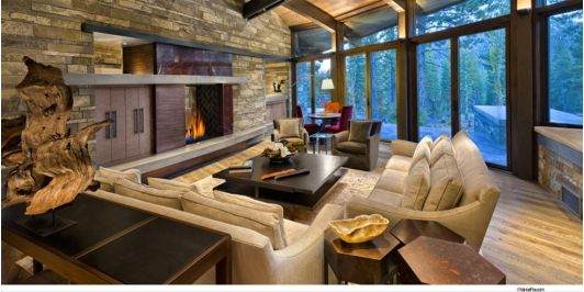 Spacious living room with a rustic look. Floor to ceiling windows gives the room a more natural feel.