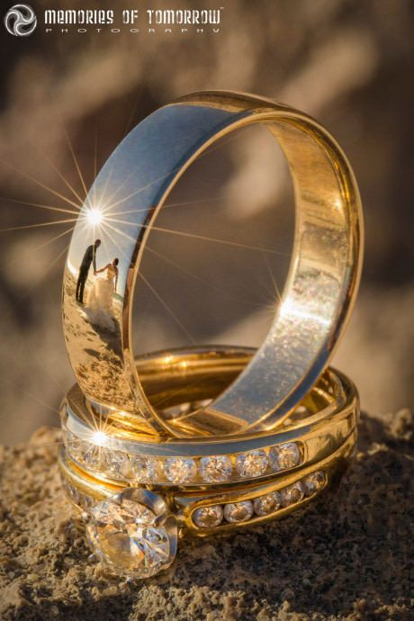 This wedding ring photo has reflections of the newlyweds