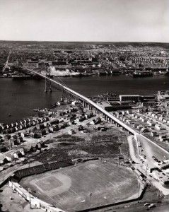 !954 snapshot of the MacDonald Bridge under construction & Little Brookklynn ball field, home of the Dartmouth Arrows, now the site of the Holiday Inn Harbourview.  The aircraft carrier in the background is the HMCS Magnificient http://www.MervEdinger.com