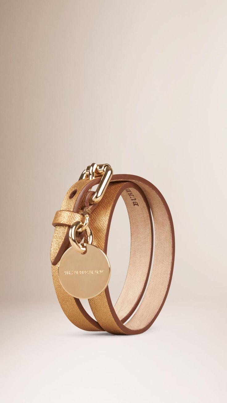Brazalete envolvente estrecho confeccionado en piel granulada metalizada. El brazalete presenta un cierre de hebilla en metal pulido y se culmina con un adorno de disco metálico y bordes tintados a mano.