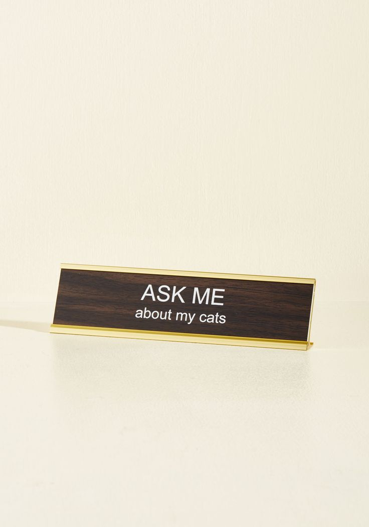 Purr Our Conversation Desk Plaque. Add a charming ice-breaker to your workspace by placing this desk plaque in easy eyeshot! Inviting passersby to inquire about your feline friends, this woodgrain-inspired, gold-trimmed nameplate embellishes your desk with a beautifully quirky touch.