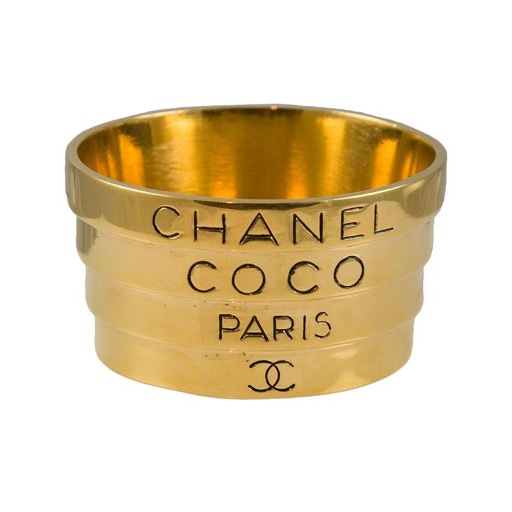 "Runway Bracelet by Chanel  France  1980's  Unusual fixed telescoping bracelet from the runway of Chanel. This bracelet is very unusual and is somewhat heavy. Gold plated metal featuring the words ""Chanel, Coco, Paris and the Locking C's"". Bracelet is 3"" at largest end and 2.5"" at smallest."