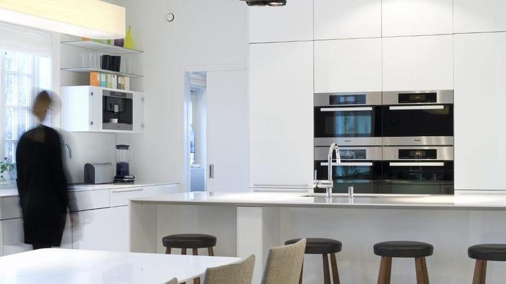 LEKKER LØSNING: Her ser du litt av den renoverte inngangen til kjøkkenet. Hvite terrazzofliser på gulv og en høyglans, hvit kjøkkninnredning gjør rommet lyst og vennlig.  FOTO: Rolf Estensen