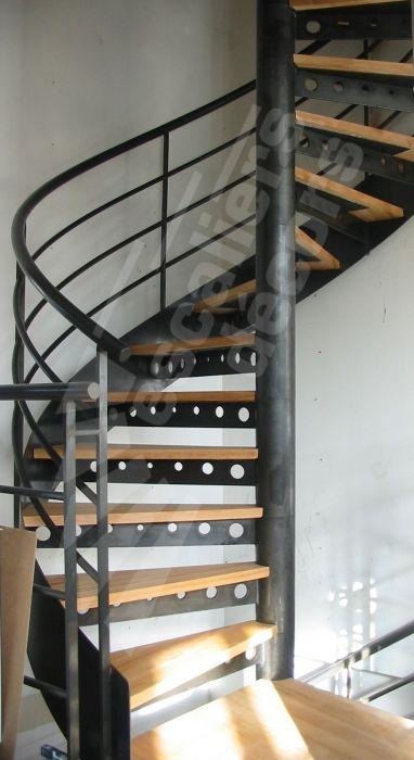 Photo DH77 - SPIR'DÉCO® Standing. Escalier intérieur en colimaçon, métal et bois pour une décoration design et contemporaine type loft. Marches type plateau bois massif sur une platine renforcée par une console métallique avec trous ronds décoratifs. Option limon formant ruban en tôle roulée en extérieur des marches soulignant les courbes de l'escalier hélicoïdal. Rampe contemporaine composée d'une main courante ergonomique en tube et de 3 sous-lisses. Escaliers Décors®.