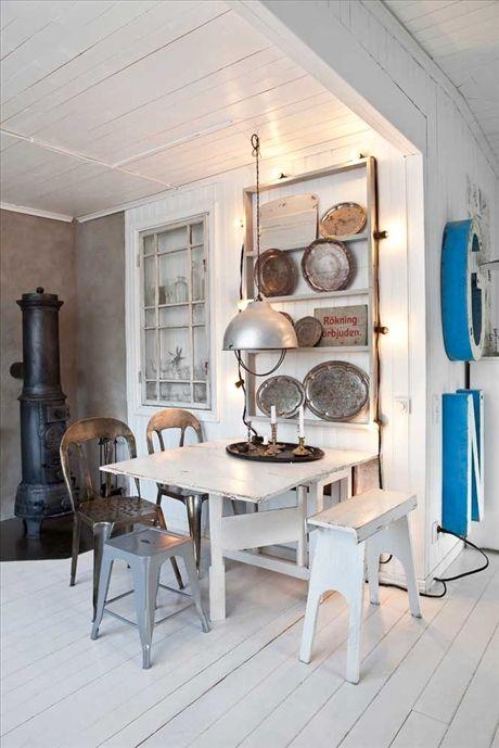 Tallrikshyllan full med antikfynd har Lulzim byggt. Intill bordet ett inbyggt skåp med fönsterruta från farmors gård som dörr.