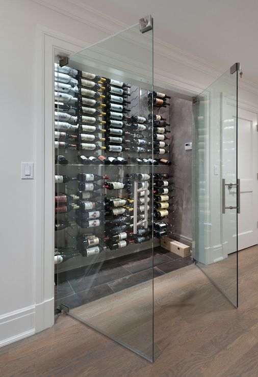 Seamless glass double doors open to a wine closet fitted with floor to ceiling wine racks.
