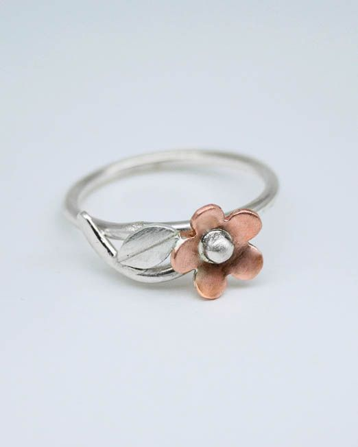 Sweet and simple copper daisy ring this lovely ring is a must for everybody's jewellery box.  Suitable for all occasions.  The daisy has been hand saw pierced from copper then lightly domed and completed with a silver bead and lightly brushed finish. From the base of the daisy is a silver stem with single silver leaf.  The band is 1.5mm wide with a lightly polished finish. The daisy measures 8.5mm in diameter.