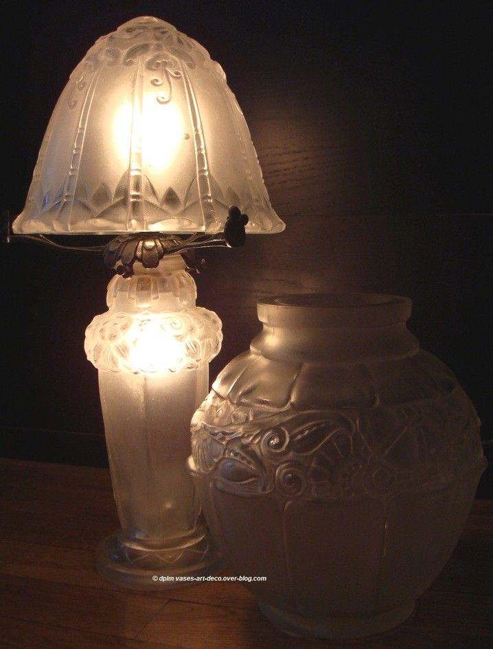 LORRAIN (1925-1934), lampe veilleuse Lorrain Nancy attribuée à Pierre d'Avesn. Verre blanc aux reliefs polis et fond dépoli sablé. Décorée d'une frise de fleurs descendantes sur l'abat jour de forme champignon et d'une couronne de fleurs dans le haut du pied hexagonal avec une base ronde à motifs triangulaires que l'on retrouve dans de nombreux modèles de Pierre d'Avesn. Monture et fivation en bronze argenté. Hauteur : 36 cm.