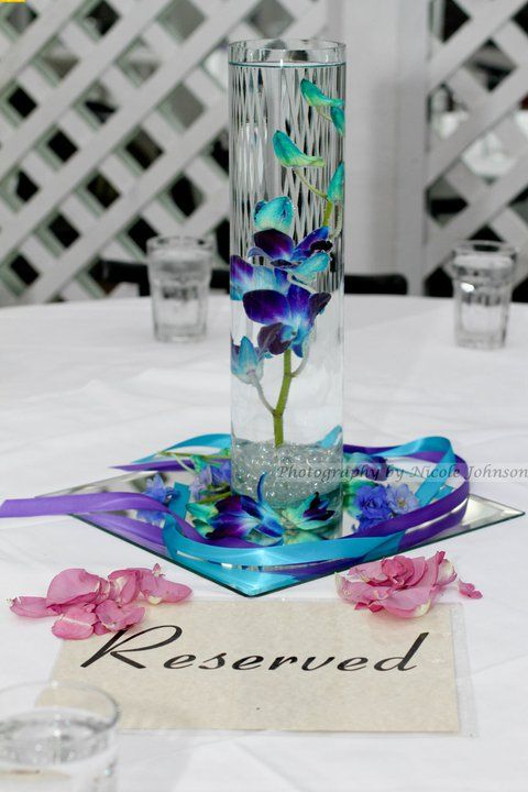 Blue orchid centerpiece on each table at the reception