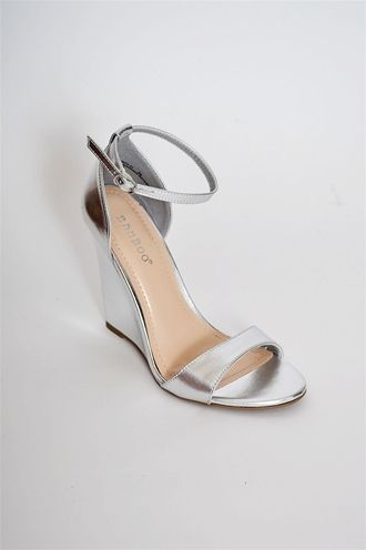 Our Metallic Must Have Wedge will be your new go to! A silver wedge with a ankle and toe strap.
