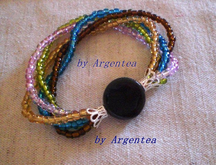 Bracciale in filo elastico con 5 fili di perline di diversi colore,leggermente intrecciati, coppette argentate all'estremità dei fili e centrale di perla piatta nera in ceramica. (7,00)  https://www.facebook.com/argentea.fantasia