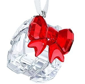 Swarovski Gift Ornament Swarovski's Christmas Gift Ornament sparkles in clear crystal with a red crystal bow. It adds a special holiday touch to any Christmas tree, festive table, or window. Decoration object. Not a toy. Not suitable for children under 15.