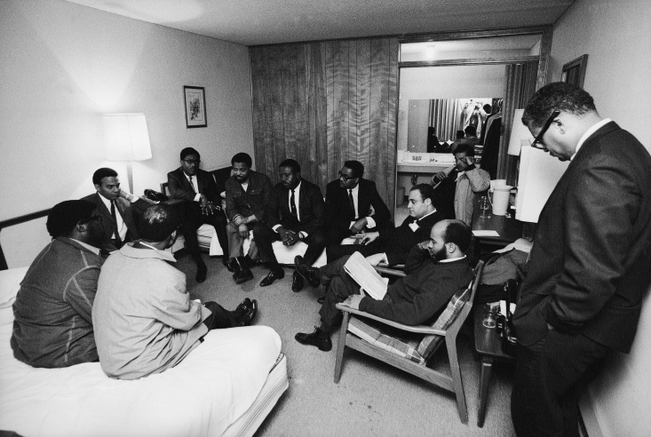 . Stunned, silent members of the Southern Christian Leadership Conference in Dr. King's room at the Lorraine Motel, April 4, 1968, including Andrew Young (far left, under table lamp) and civil rights leader and Dr. King's colleague, Reverend Ralph Abernathy, in the middle on the far bed.