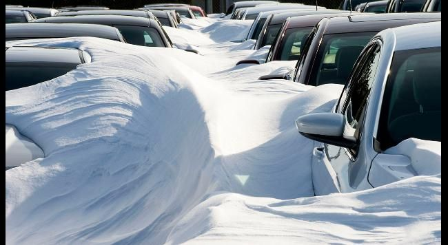 Rental cars are buried in snow, at Dulles International Airport (IAD) January 25, 2016, outside Washington, DC, in Sterling,Virginia after Winter Storm Jonas