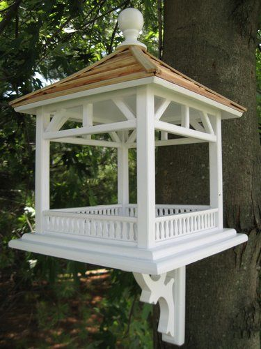 """This fly-through gazebo feeder is perfect for just about any setting. Constructed of exterior grade ply-board, and topped with a pine shingle roof, the large open area can be used with seed or can easily accommodate a piece of fruit for Orioles to enjoy. Item Dimensions: 18"""" H x 14"""" W x 14"""" D All of our pieces are intended for use outdoors. Each is fully functional, with removable back walls for easy cleaning. The hole openings are designed to accommodate common cavity dwellers such as…"""